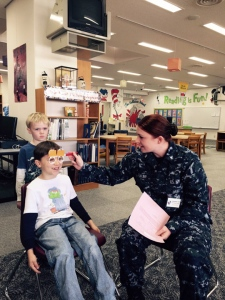 HM3 Emily Fowler, USNH Yokosuka Directorate of Public Health administers a vision screening to two students from The Sullivans School during an annual vision and hearing screening visit to the Yokosuka Complex of Schools. During a six-day period 870 students were screened at the Ikego and Sullivans Elementary Schools and the Yokosuka Middle School. (Photo by Shawn Bogen)